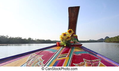 ornamented and decorated longtail boat drifts along river -...