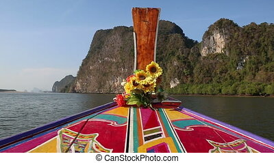 ornamented and decorated longtail boat sails up to cliffs -...