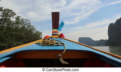 wooden longtail boat floats along river - wooden decorated...