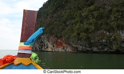 view of fabric flapping on longtail boat drifting past cliff...