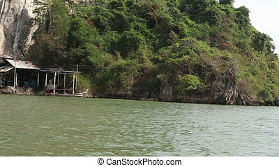 view of moorage at foot of rocky island with mangrove trees...