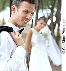 handsome groom smiling and looking at camera - portrait of...