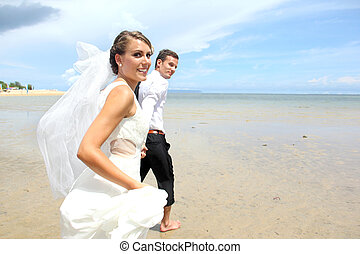 newlywed couple running at the beach