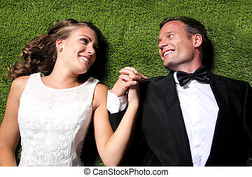 newlywed couple lying on the grass and holding each other...