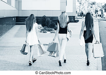 Shopping - Girls holding shopping bags and walk around the...