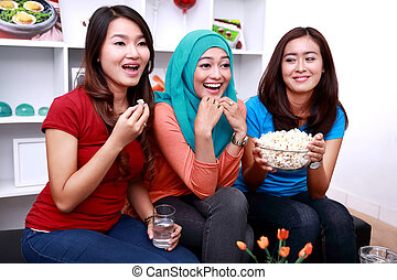 three young women look excited when watching a movie