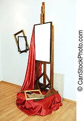 easel, red drapery and frames in studio of painter,...