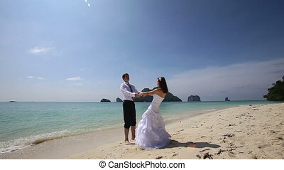 bride and groom turn around holding hands on beach - cute...