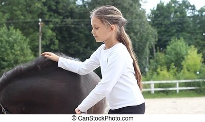 girl stroking pony - beautiful little girl stroking pony