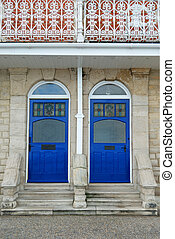 Two matching blue doors - Two blue wooden doors mirroring...