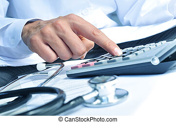 healthcare professional calculating on an electronic...
