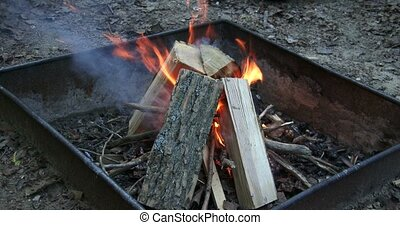 Wood burning in fire pit - Big pieces of wood burning in...