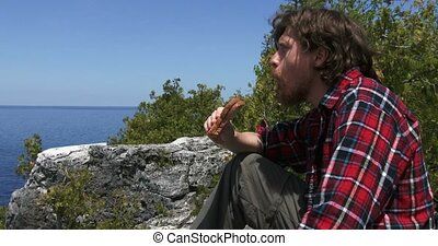 Hiker resting and eating a sandwich - Hiker resting on a...