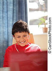Young smiling boy doing looking at a computer wearing...