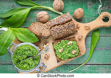 Ramson, wild garlic and sauce pesto on a wooden table