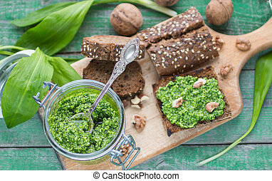 Ramson, wild garlic and sauce pesto on a wooden table