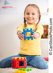 Girl with lego - Little pretty smiling girl in yellow...