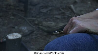 Woman sharpens stick during camping - Woman sharpening stick...