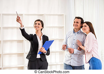 Realtor - Female realtor is showing a flat to young couple.