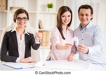 Realtor - Female realtor with key and young couple showing a...