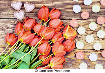 Tulips and a heart candles - Bunch of fresh red tulips lying...