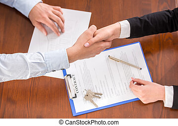 Realtor - Top view of handshake of a real estate agent and a...