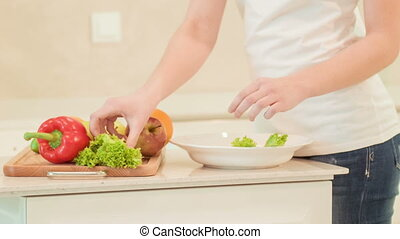 young woman putting vegetables on plate Organic food - That...