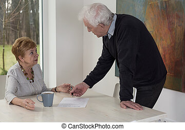 Divorce papers - Elderly man giving to his surprised wife...