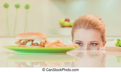 young woman choosing between healthy food and not
