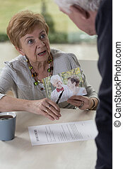 Husband with lover - Elderly irate woman showing photo of...