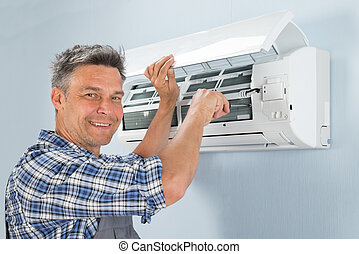 Male Technician Repairing Air Conditioner - Portrait Of A...
