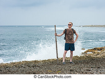 A young masculine guy is walking on the beach.