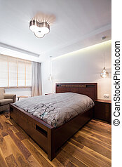 Double bed with wooden frame in luxury bedroom