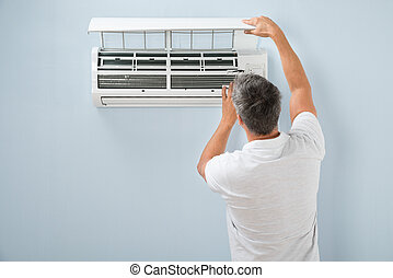 Man Cleaning Air Conditioning System - Rear View Of A Man...