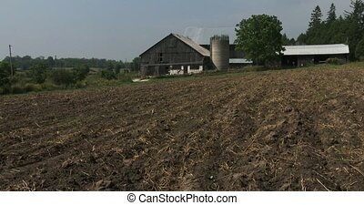 Old barn and uncultivated field in small organic farm in...