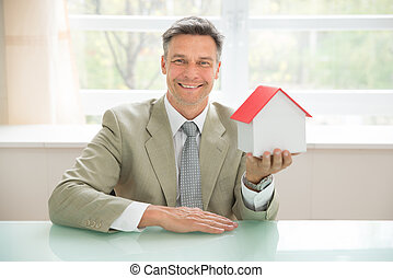 Happy Businessman Holding House Model - Portrait Of A Happy...