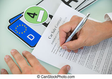 Person Filling Car Sale Contract Form - Close-up Of A Person...