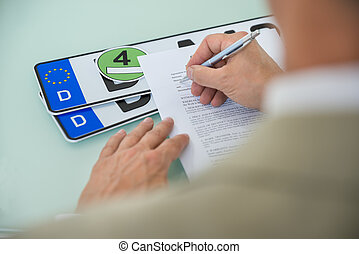 Businessman Filling Car Sale Contract Form - Close-up Of A...
