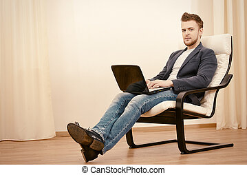 comfortable life - Happy young man using laptop sitting on...