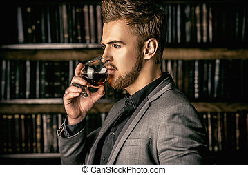 whiskey - Elegant man in a suit with glass of beverage...
