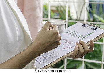 review graphics - businesswoman reviewing graphs with a cup...