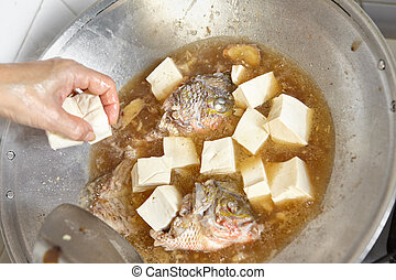 Adding tofu to the fish stew on the wok