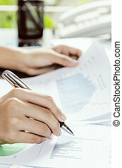 Evaluating data - Woman evaluating charts and documents on...