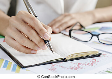 Taking note - Woman taking note with a pen