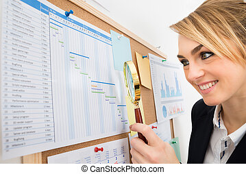 Businesswoman Examining Gantt Chart With Magnifying Glass -...