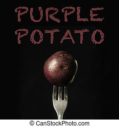 Purple potato on a fork on a black background
