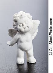 Angel - a small cute ceramic angel statuette over a dark...