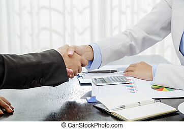 Successful businesswoman shaking hands in office