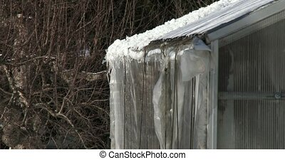 Snow melting on roof of greenhouse