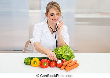 Female Dietician Examining Vegetables - Happy Female...